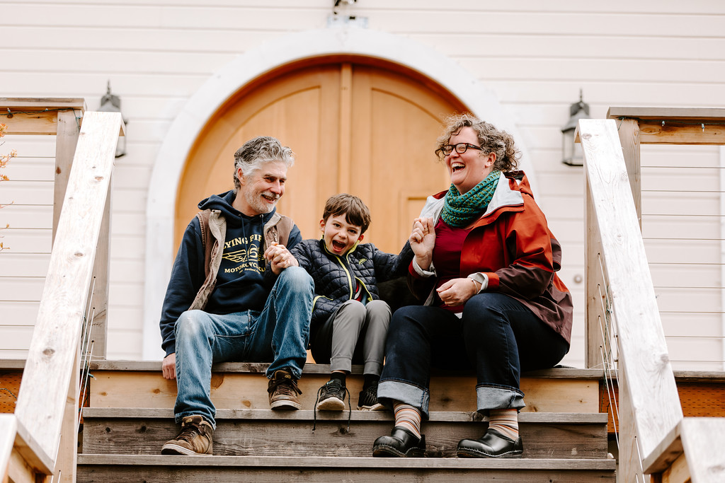 John, Clyde and Erin Telford, winners of the contest, sitting on the front steps outside of their home on SE 62nd Ave